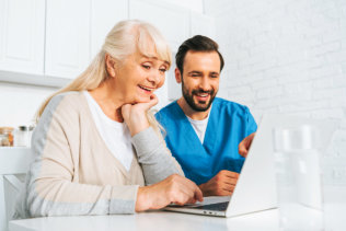 caregiver and senior woman using a laptop