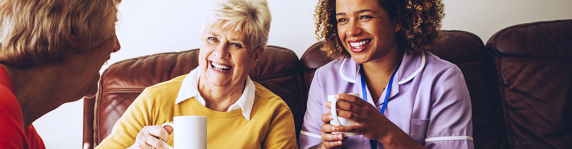 caregiver and two seniors are laughing