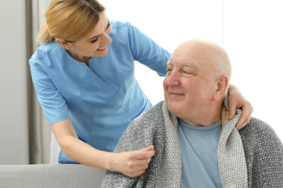a nurse giving a blanket to and elderly