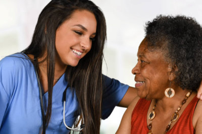 a nurse smiling at an elderly