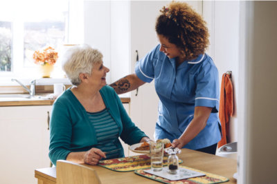 a nurse giving food to an elderly